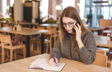 Young woman accountant talking on cell phone and writing