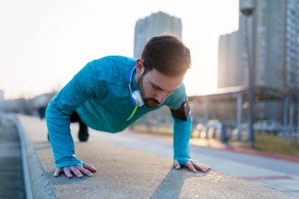 Young handsome man doing push up training outdoors