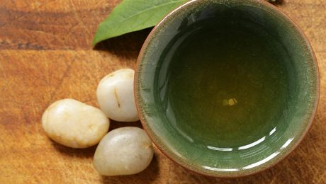 Glass of green tea with some polished pebbles.