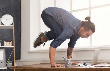 Man doing yoga on his desk