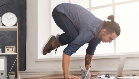 Man doing yoga on his desk