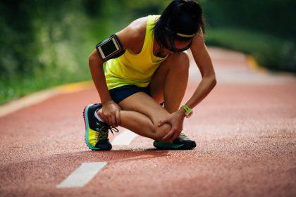 Female runner suffering with pain on sports running knee injury